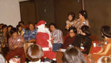 """Kellogg Chan's Christmas"" Gerald Jann dressed up as Santa Clause talking to two women..."
