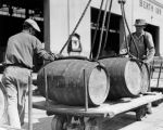 Liquor barrels lifted onto carts