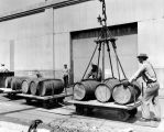 Barrels of liquor lifted onto carts