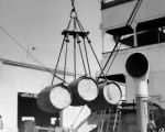 Closeup view, liquor barrels hoisted by ropes