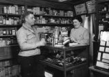 Sales interaction at Heath Drug Store counter, view 2