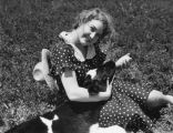 Woman in polka-dot dress feeding a calf