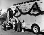 Bert Thomas and young patrons next to an LAPL Bookmobile