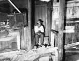 Man sits in doorway of his dilapidated home