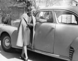 Lady standing by a man in a car