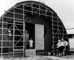 A young family outside their quonset unit