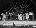 Cast members rehearse a finale on stage