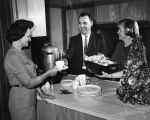 Mrs. Ruth Neve, left, starts program with cup of coffee