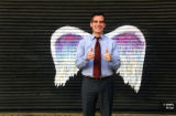 "Mayor Eric Garcetti giving a ""thumbs up"" and posing in front of a mural depicting angel..."