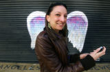 Unidentified woman holding cell phone posing in front of a mural depicting angel wings