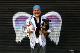 Downtown resident Michael Hudson-Medina holding two dogs and posing in front of a mural depicting...