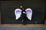 Unidentified man with scissors posing in front of a mural depicting angel wings