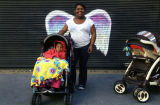 Unidentified woman and a child in stroller posing in front of a mural depicting angel wings