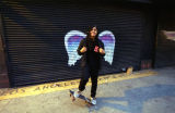 Unidentified man with skate board posing in front of a mural depicting angel wings