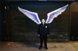 Unidentified security officer posing in front of a mural depicting angel wings
