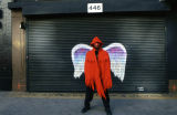 Unidentified person in a red hooded cape and mask posing in front of a mural depicting angel wings