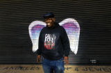 Unidentified man in a cap and sweatshirt  posing in front of a mural depicting angel wings