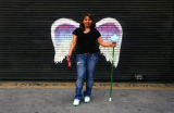 Unidentified woman holding mop and soda bottle posing in front of a mural depicting angel wings