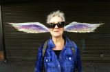 Unidentified woman in sunglasses posing in front of a mural depicting angel wings