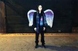 Unidentified woman with scarf posing in front of a mural depicting angel wings