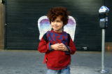 Unidentified child in red shirt posing in front of a mural depicting angel wings
