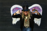 Unidentified man in costume and sunglasses posing in front of a mural depicting angel wings