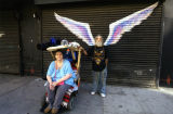 Unidentified man with woman in a wheelchair posing in front of a mural depicting angel wings