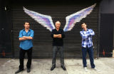 Three unidentified men posing with arms crossed in front of a mural depicting angel wings