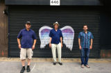 Three unidentified men posing in front of a mural depicting angel wings