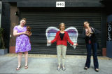 Katie Dunham, Louise Steinman, and an unidentified woman posing in front of a mural depicting...