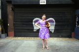 Katie Dunham posing in front of a mural depicting angel wings