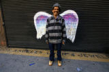 Unidentified man in striped hoodie posing in front of a mural depicting angel wings