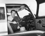 Actor Robert Horton sitting in an airplane with poodle