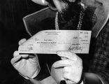 Hedy Lamarr displays check for $9000