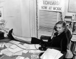 Carole Lombard, press agent, props feet on desk