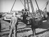 Oil field workers move heavy equipment