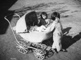 Children and baby carriage in the Santa Cruz Adobe courtyard