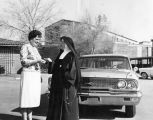 Mrs. Charles Stein gives key to new car to Sister Mary Vincent