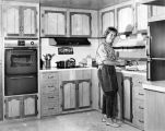 Mrs. Joseph Kelly prepares beef stroganoff in her mobile home in Pacoima park