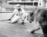 Jungleland wild animal trainer Dick Walker is imitated by his well-trained lion associate