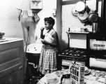 Girl brushes teeth in kitchen, slum dwelling