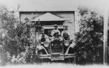 Japanese American boys sitting on car