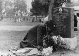Woman tending husband's grave