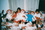 Siblings on couch with dolls