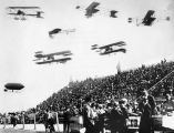 6 biplanes and 1 airship over crowd