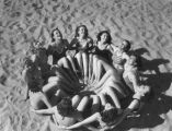 Young women form a circle on the sand