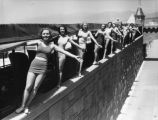 Women standing on wall at Deauville Club