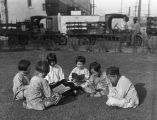 Chinese chidren sitting on the grass reading