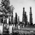 Oil derricks by a cemetery