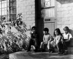 Children sitting outside their apartments